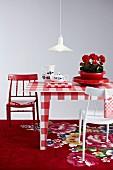 Rot-weisser Mustermix mit kariertem Tisch und farbig lackierten Stühlen auf Blumenteppich