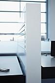 Halbhohe Trennwand und beidseitige Schreibtische vor Loftfenster