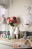 Collection of delicately patterned china teacups, china figurines and vases with bouquet of roses on marble cabinet top against wall with stucco reliefs