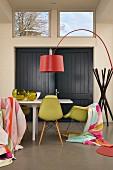 Esstisch mit drapierten Tüchern auf Klassikerstühlen, rote Designer-Bogenleuchte und Garderobenständer im Hintergrund