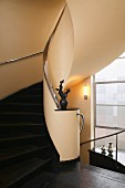 Elegant, curved staircase with black stone steps, chrome handrail and sculpture on newel
