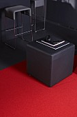 Grey designer pouffe on red rug with bar stool in background