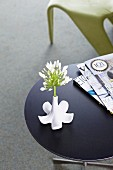 White allium in white, designer vase formed as inverted china flower next to stack of magazines on side table