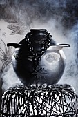 Gothic arrangement of black ceramic pot, necklace with spider pendant and wire mesh stool in front of clouds of smoke