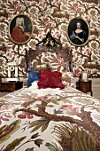 Grand bedroom with bed linen and wallpaper in matching floral pattern and oval historical portraits on wall