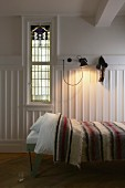 Single bed with striped bedspread, white-painted walls and wooden dado and window with Art Deco elements in traditional ambiance