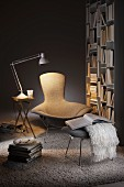 Designer easy chair and footstool between table lamp on folding table and bookcase