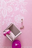Top view of bras on pink armchair and fuchsia side table on pink rug with white floral pattern