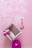 Blick von oben auf rosa Sessel mit Damenwäsche und fuchsiafarbener Beistelltisch auf rosa Teppich mit weißem, floralem Muster