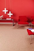 Red lounge chairs, white, cross-shaped pendant lamps and side table against red wall