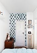 Blick über Bett auf weisse Zimmertür und tapezierte Wand in schmalem Raum