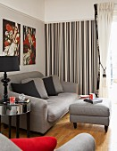 Grey sofa set with ottoman in living room with striped wallpaper on accent wall and pale grey wall