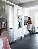 Frau im Hintergrund in zeitgenössischer Küche, weisse Einbauschränke und integrierter Kühlschrank aus Edelstahl