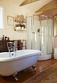 Freistehende Badewanne und moderne Duschkabine in einem Wohnbad mit Antikkommode und Orientteppich auf dem Dielenboden