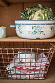 Cauliflower in enamel bowl & wire basket of towels on dresser