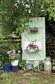 Planted, vintage washstand against mint-green board door in garden