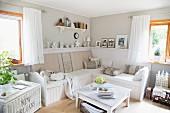 Gemütliche Wohnzimmerecke mit weiss lackiertem Couchtisch und Sitzbank in hellgrau getönter Zimmerecke mit Vintageflair