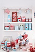 Red and blue, country-house-style crockery on bottle rack and wall-mounted shelving unit