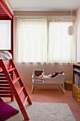 Puppenwiege weiss lackiert vor Fenster mit geschlossenem Vorhang, seitlich teilweise sichtbares Hochbett mit Leiter aus hellrot gebeiztem Holzgestell