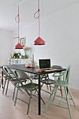 Vintage folding chairs and high chair painted green around black metal table below pendant lamps with pink lampshades