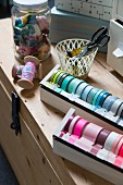 DIY dispenser for various washi tapes and sewing utensils on top of wooden trunk