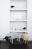Figurines of birds and crockery on shelving in niche behind sheep sculptures