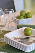 Lime and cutlery on stacked plates next to wine glasses