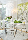 Bowl of fruit on white dining table and modern chairs on flokati rug next to fabric wall hanging