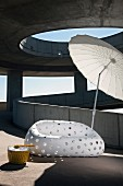 Designer outdoor sofa in white plastic with perforated pattern and Oriental parasol on sunny concrete ramp