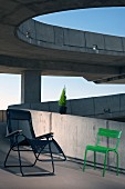 Metal tube lounger with mesh seat and grass green outdoor chair on ramp of concrete building