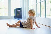 Little girl sitting on floor in living room