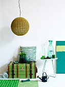 Arrangement in shades of green - pendant lamp with wicker lampshade, steamer trunk and ornaments on side table