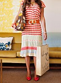 Woman wearing striped summer dress carrying polka-dot bag in front of mustard retro velvet sofa