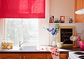 Window with red fabric roller blind above stainless steel sink in romantically decorated kitchen with wooden doors