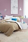 Bettwäsche im Punktedessin auf Doppelbett in romantisch gestaltetem Schlafzimmer, pastell lila Farbton an Wand