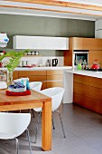 White shell chairs around wooden table in kitchen with modern counters, solid wooden fronts on base units and grey-painted walls