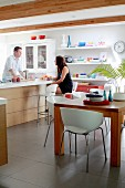 White shell chairs around wooden table and couple at modern counter with bar stools in background in kitchen with floating shelves