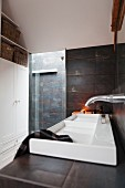 Designer sink against wall with dark metallic tiles and shower area in background