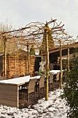 Stühle an langer Tafel unter Pergola aus Geflecht auf Baumstämmen in winterlichem Innenhof