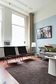 Klassikerstühle, schlichtes Sofa und dunkelgrauer Wollteppich auf Edelholzparkett in hohem Altbauwohnraum