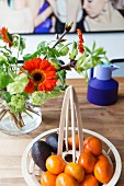 Designer bowl of fruit and bouquet with gerbera daisies on dining table