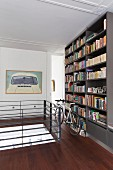 Bicycle in front of bookcase on landing