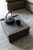 Black teapot and tea bowl on wooden crate on grey, speckled, woven carpet