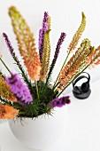 Flower spikes of various colours in white vase