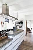 Designer island counter below extractor hood in open-plan kitchen
