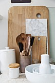 White crockery and various wooden spoons in jar in front of chopping boards