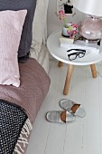 Slippers next to bedside table with table lamp and black spectacles
