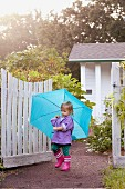 Little girl walking in garden carrying umbrella