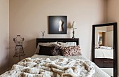 Mirror, bed and wire mesh tailors' dummy in modern bedroom