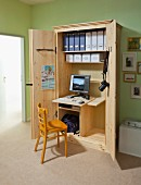 Wooden chair in front of DIY, open office cabinet with integrated desk, monitor and box files